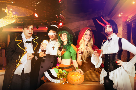 Group of friends in club at the party in halloween costumes