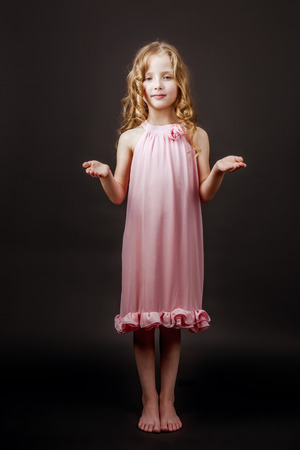 modesty: Charming little girl stands barefoot in pink dress on the black wall backdrop
