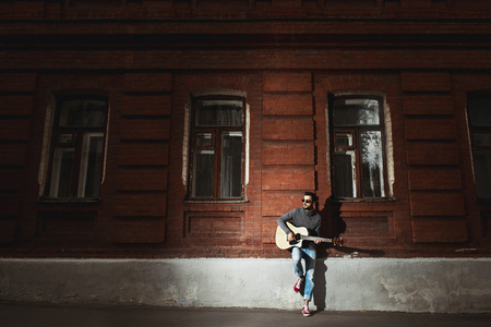 gitar: Man stands on brick wall and plays the gitar concept