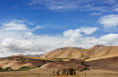 aktru: Mountais with trees on the blue cloudy sky