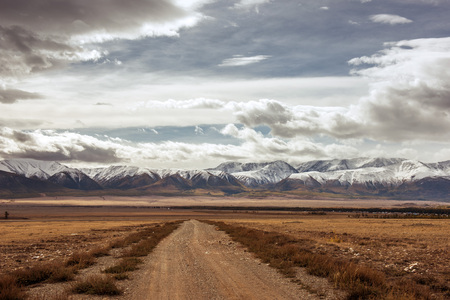 vineyard plain: Old highway goes to montains and cloudy sky Stock Photo