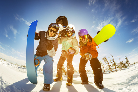 Bright color snowboarders posing on blue sky backdrop. Sheregesh, Siberia, Russia