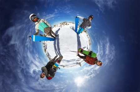 Little planet with bright color snowboarders posing on blue sky backdrop. Sheregesh, Siberia, Russia Фото со стока