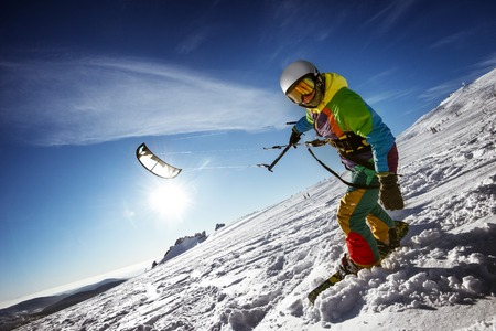 kiter: Bright color Snowboarder skydives on blue sky backdrop. Sheregesh, Siberia, Russia