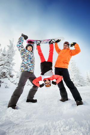 Bright color snowboarders posing upside down on blue sky backdrop. Sheregesh, Siberia, Russia