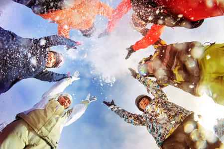 Bright color snowboarders throw snow on blue sky backdrop. Sheregesh, Siberia, Russia Stok Fotoğraf