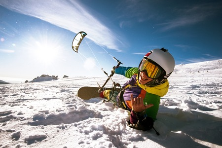 kiting: Bright color Snowboarder skydives on blue sky backdrop. Sheregesh, Siberia, Russia