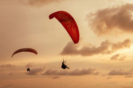 スカイダイバーは、曇り空の背景の背景に飛ぶ