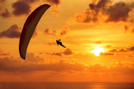 Silhouette of skydiver on background sunset and the sea Standard-Bild