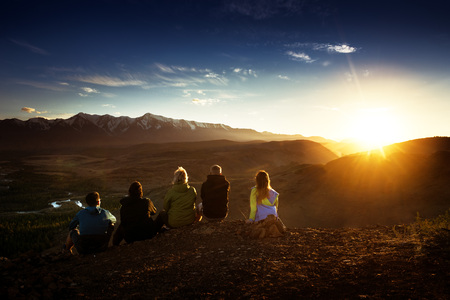 Group of friends sits on the mountains top on background of mountains and sunset Stok Fotoğraf
