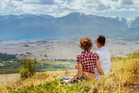 Loving couple sits on mountain backdrop and enjoying view of nature at sunny day in summer