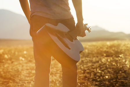 Closeup photo of man with guitar on sunset backdrop Фото со стока
