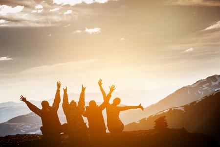El grupo de amigos se sienta en la cima de la montaña y se divierten en las montañas telón de fondo Foto de archivo - 66073561