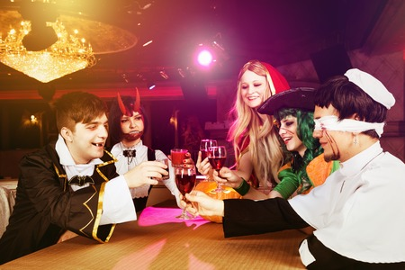 Group of friends having party in halloween costumes at night club