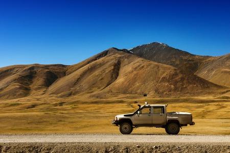 Mening van de auto SUV op de grote bergenachtergrond