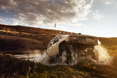 自動車の SUV はオフロードと上空の背景上に水を克服します。 写真素材
