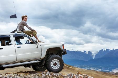 남자는 차에 앉는다 산에는 SUV가 배경 바퀴