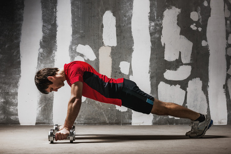 Man doing push ups on dumbbells on empty concrete backdrop Stock Photo