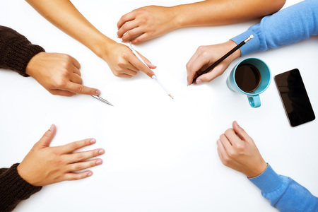 Group of people sits at the table. Hands closeup work space. Top view
