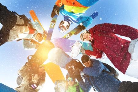 サークルと笑みを浮かべて立っている幸せなスキーヤーとスノーボーダーのグループ