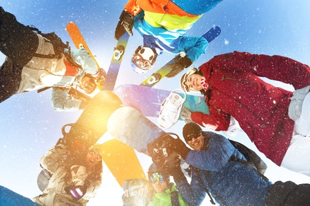Group of happy skiers and snowboarders stands in circle and smiling Фото со стока