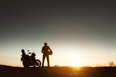 Biker's silhouette with motorcycle and helmet in hands on sunset backdrop