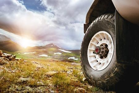 Groot autowiel op bergen en zonsondergangachtergrond. Offroad 4x4-concept