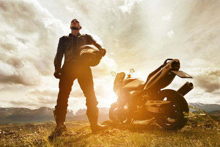 Biker stands with motorcycle and helmet on mountains backdrop