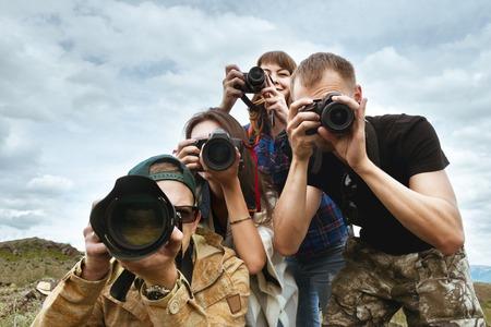 一緒に写真を撮る友人カメラマンのグループ 写真素材