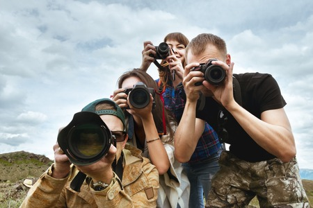 Group of friends photographers taking photo together