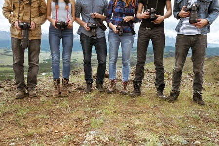 Group of travel photographers stands on line with cameras in hands. Team and teamwork concept 免版税图像