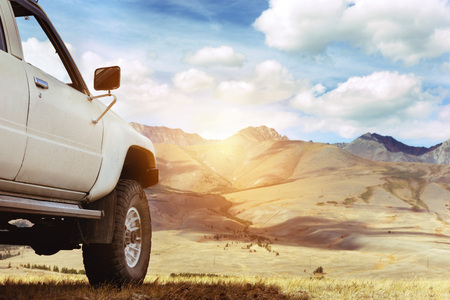 SUV car against mountains. 4x4 offroad concept. Space for text