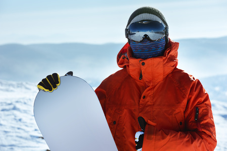 Man snowboarder stands with snowboard. Closeup portrait. Red jacket 스톡 콘텐츠
