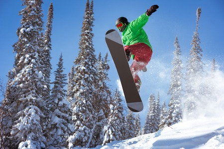 Snowboarder jumps in forest. Freeride snowboarding in Sheregesh ski resort Stockfoto