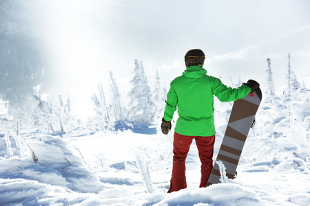 Snowboarder stands with snowboard on the top of mountain on forest backdrop. Sheregesh ski resort