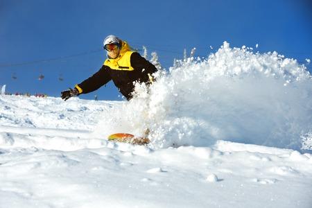 Fast snowboarder downhill in powder. Extreme slope winter ski sports