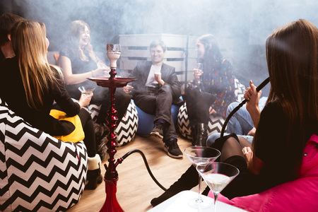 Group of young friends relaxing in shisha club-bar Stockfoto