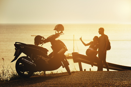 Happy couple sunset sea motorcycle road