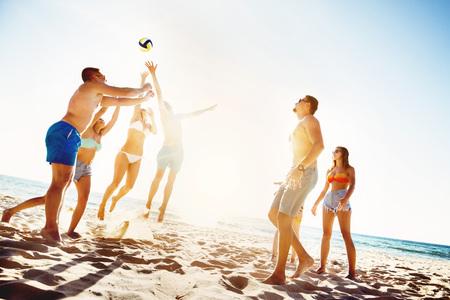 Friends playing beach voleyball sunset time