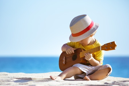 Little boy plays guitar ukulele at sea beach