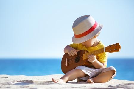 Kleiner Junge spielt Gitarre Ukulele am Meer Strand