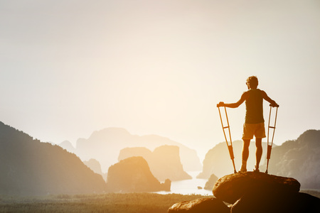 Disabled man with crutches on big rock stands like winner