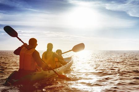 Familie van vader moeder en zoon kajakken op zee zonsondergang