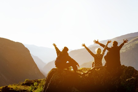 Happy friends at sunset in mountains range