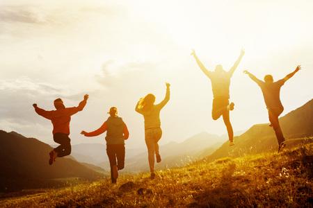 Groep gelukkige vrienden rennen en springen Stockfoto