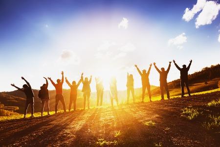 一緒に夕日に腕を上げる友達の大きなグループ 写真素材
