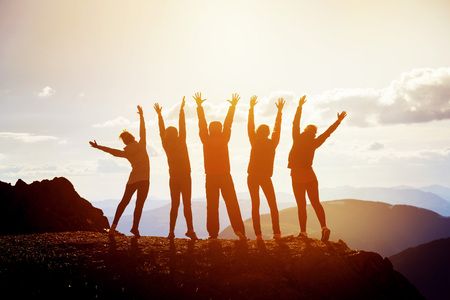 Five happy friends with raised arms Foto de archivo