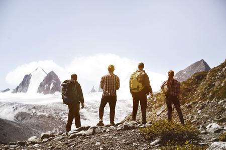 Group four friends trekking mountains