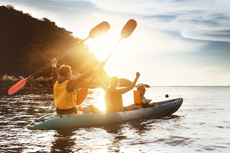Happy family kayaking sunset sea