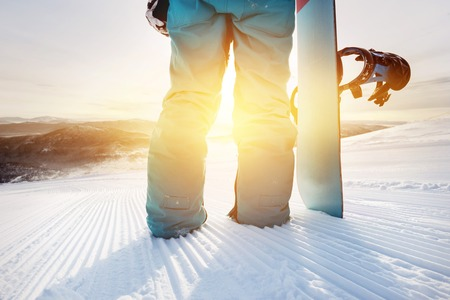 Closeup snowboarder at ski slope with snowboard Stock Photo
